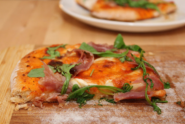 ein Stück hausgemachte Pizza mit Schinken, Rauke und Mozzarella