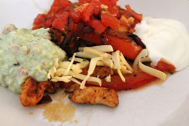Hühnchen, Paprika, Tomatensalsa, Guacamole, Saure Sahne und Käse für die Chicken Fajitas