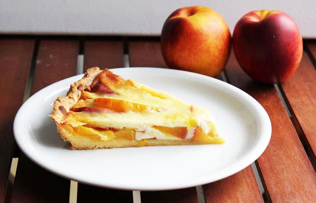 ein Stück frisch gebackene Tarte mit Nektarinen und Vanillecreme
