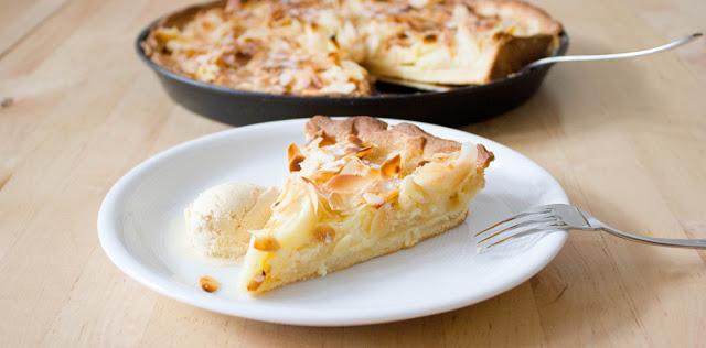 ein Stück frisch gebackene Tarte mit Äpfeln, Mascarpone, Mandeln und Vanilleeis