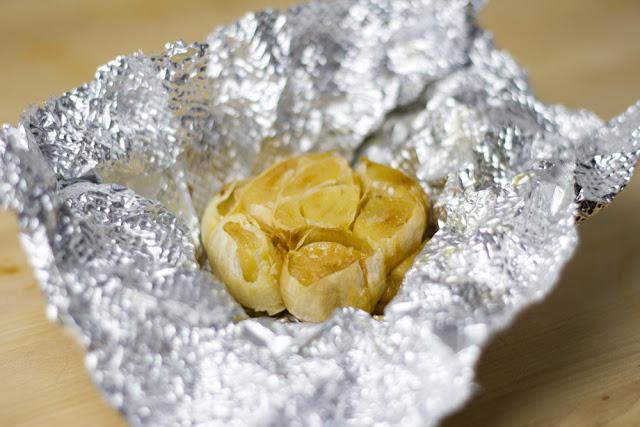 eine ganze Knoblauchknolle wird in Alufolie im Ofen geröstet