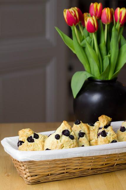 frisch gebackene Scones mit Heidelbeeren und Sahne auf dem Frühstückstisch