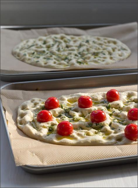 Teig für Focaccia mit Rosmarin und Meersalz und Tomaten mit Kräutern, vor dem Backen auf dem Backblech