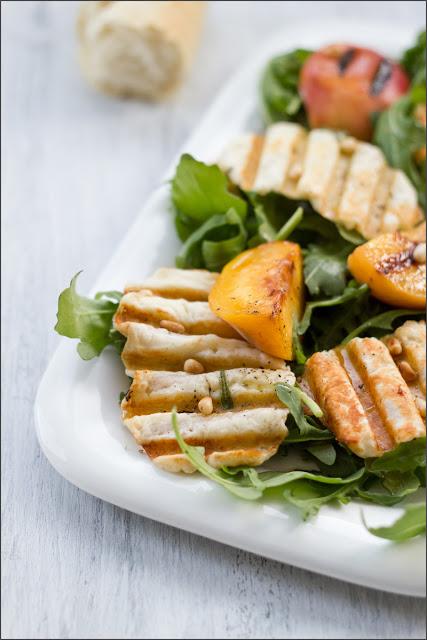 auf einer Platte angerichteter Sommersalat mit knusprigen Halloumi-Chips und gegrillten Pfirsichen