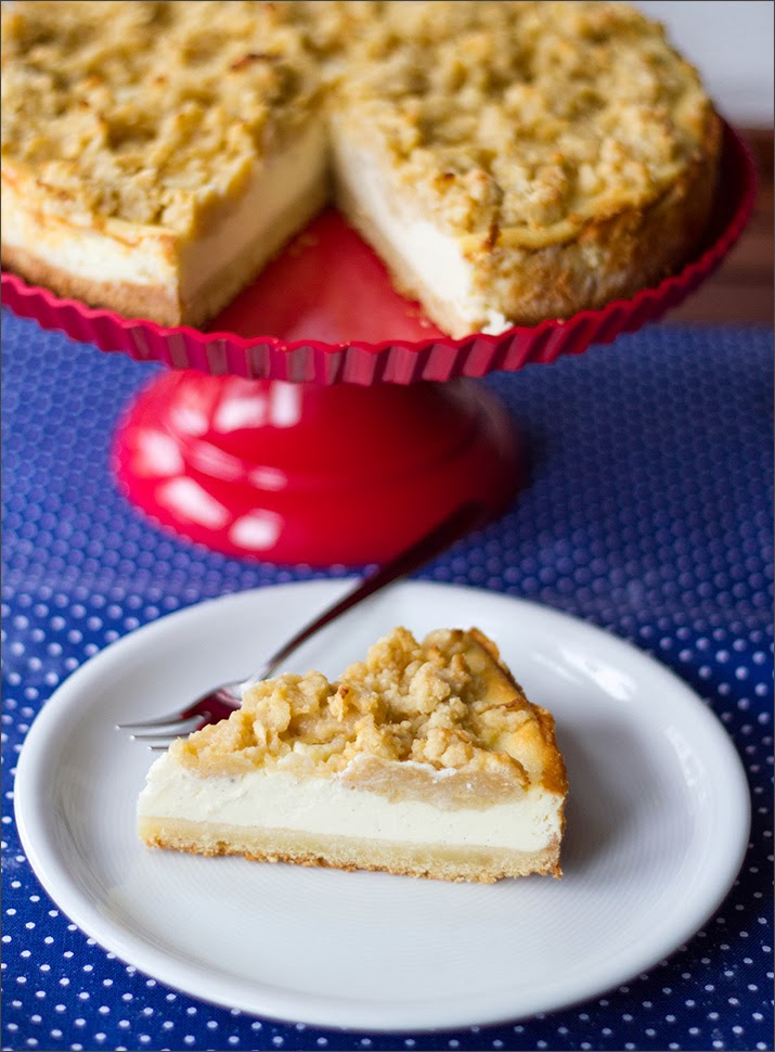 Angeschnittener Vanille-Käsekuchen mit Apfel-Streuseln auf Kuchenplatte, Kuchenstück auf Teller
