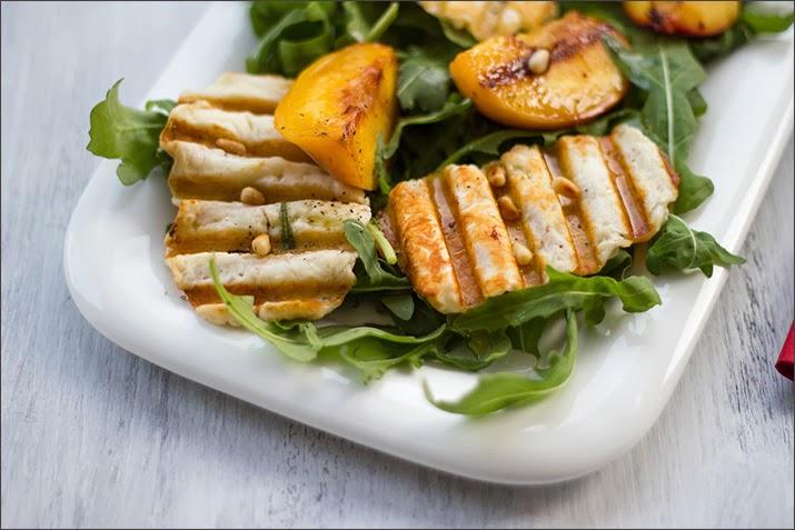 Angemachter Rucola-Salat mit knusprigen Chips aus Halloumi, gegrillten Pfirisichen, Kräutern und Zedernüssen