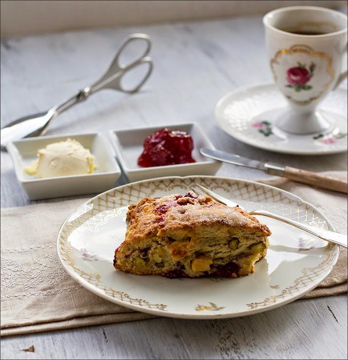 Scones mit Himbeeren, Pistazien und weißer Schokolade zum Sonntagsfrühstück oder der Tea Time, serviert mit Clotted Cream und Erdbeerkonfitüre