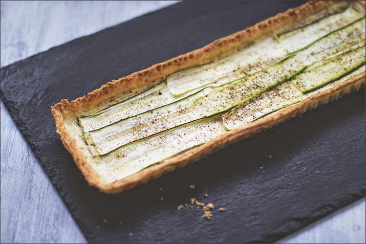 Frisch gebackene Zucchini-Ziegenkäse-Tarte mit Parmesan, auf einer Schieferplatte