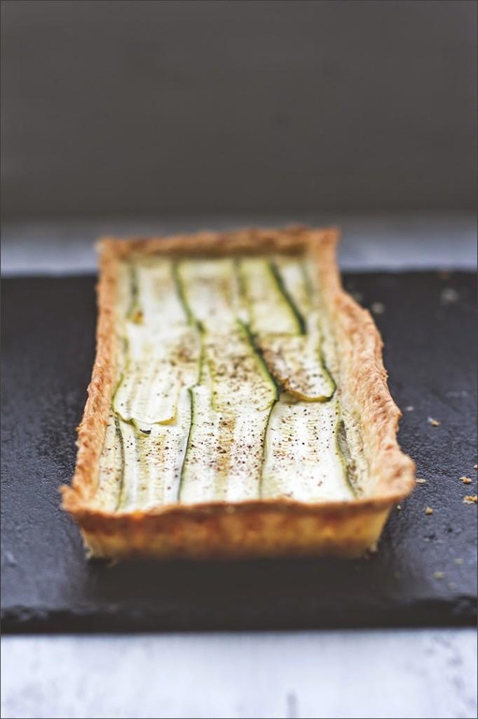 Zucchini-Ziegenfrischkäse-Tarte mit Parmesan, serviert auf einer Schieferplatte