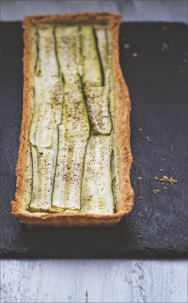 Zucchini-Ziegenkäse-Tarte mit Parmesan, angerichtet auf einer Schieferplatte