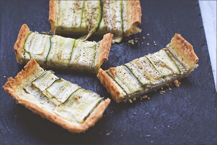 Zucchini-Ziegenkäse-Tarte, angeschnitten auf einer Schieferplatte serviert