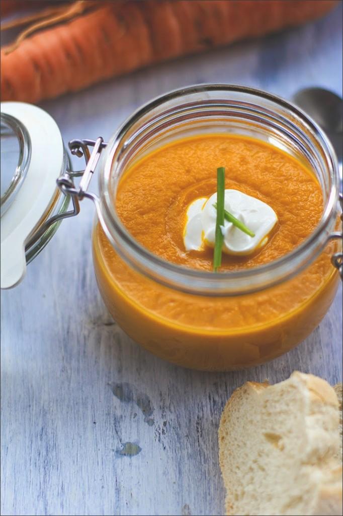 Vegetarische Möhrensuppe / Karottensuppe, serviert mit griechischem Joghurt und Schnittlauchröllchen im Bügeglas