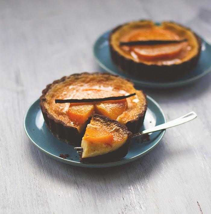 Angeschnittene Kakao-Tartelettes mit einer Füllung aus weißer Schokolade und Sahne, belegt mit Kakis in Vanillesirup