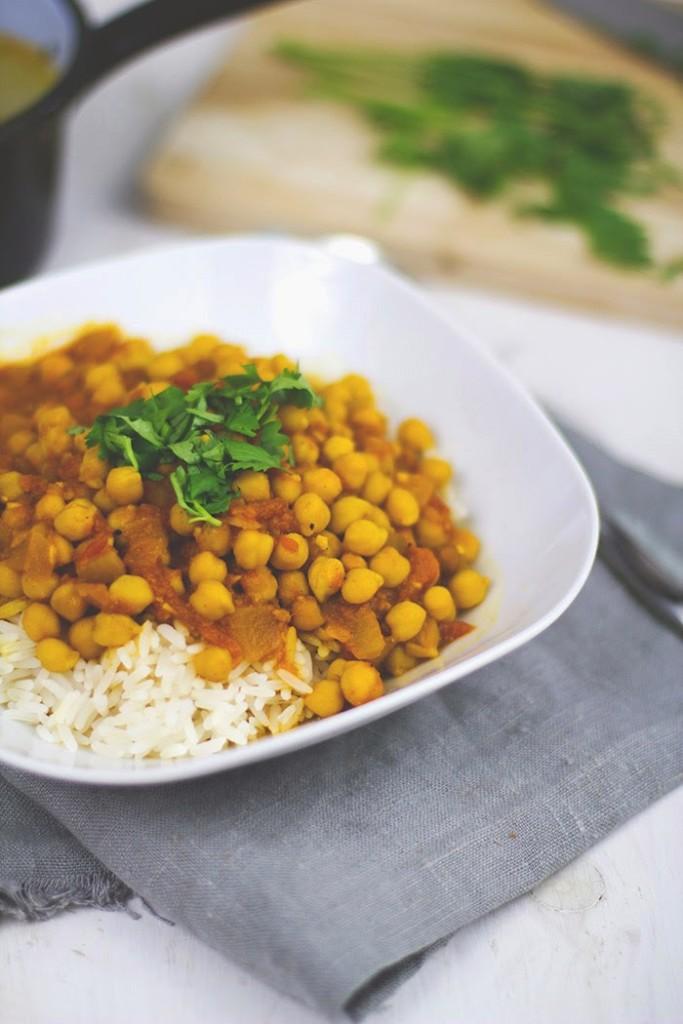 ein großer Teller Kichererbsen-Curry mit Tomaten auf Reis, bestreut mit Koriander