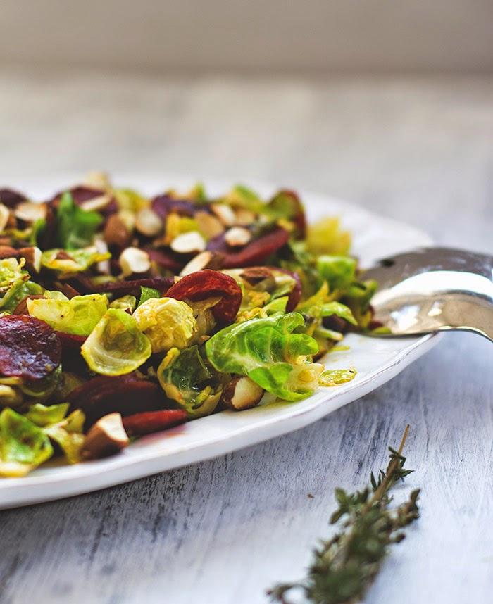 frischer Salat mit Rosenkohl, Chorizo und Mandeln auf einem Teller