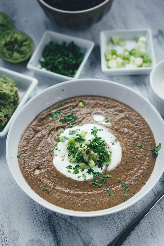 Rezept für vegetarische schwarze Bohnensuppe mit Guacamole, saurer Sahne, Limette und Koriander | moeyskitchen.com #rezepte #foodblogger #suppe #bohnen #schwarzebohnen #guacamole #vegetarischerezepte #vegetarischkochen #veggie