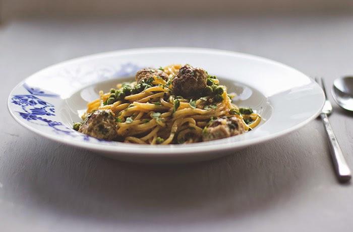 frisch gekochte Portion Spaghetti mit Meatballs, Erbsen und Sahnesauce