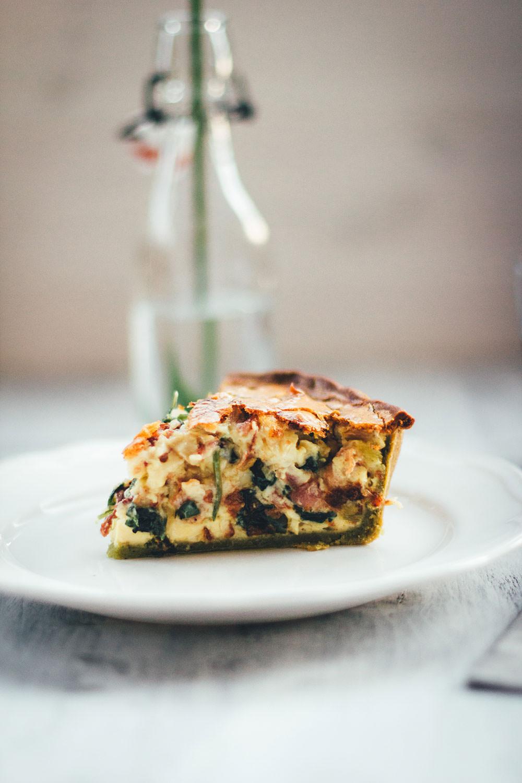 Rezept für deftige Spinat-Bacon-Quiche mit grünem Spinat-Ricotta-Boden | gefüllt mit knusprigem Bacon, würzigem Cheddar und frischem Spinat | moeyskitchen.com #quiche #tarte #spinat #bacon #cheddar #rezept #dinner #lunch #backen #foodblogger #rezepte