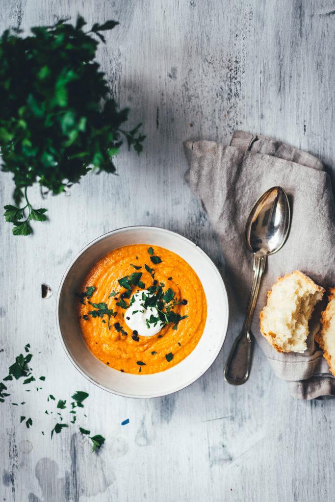 Rezept für eine würzige Rote-Linsen-Suppe mit Cayenne-Pfeffer und geräuchertem Paprikapulver. Rote Linsen und weiße Bohnen sättigen wunderbar, Möhren und Zwiebel geben der Suppe Substanz. Fein püriert und serviert mit einem Klecks Schmand und gehackter Petersilie ist es eine fantastische vegetarische Suppe für kalte Tage nicht nur im Winter!   moeyskitchen.com