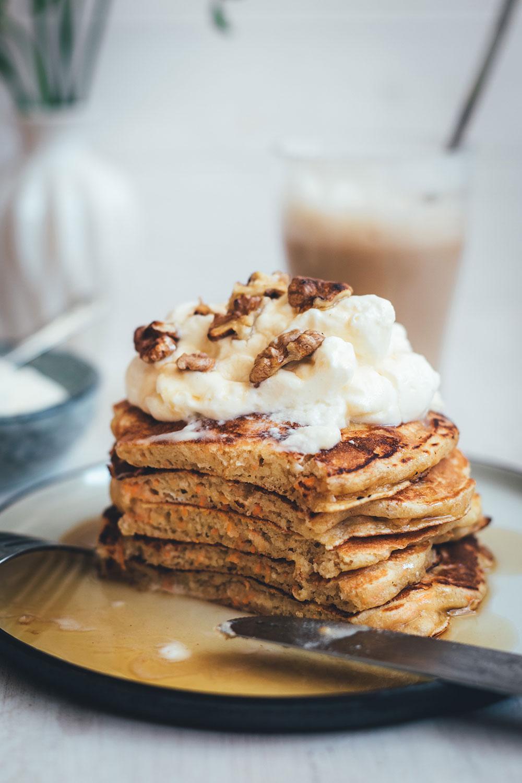 Rezept für saftige Carrot Cake Pancakes | Klassischer Möhrenkuchen verpackt in fluffig-weiche Buttermilch-Pancakes mit Frischkäse-Topping und knackigen Walnüssen | moeyskitchen.com #pfannkuchen #pancakes #frühstück #breakfast #carrotcake #carrotcakepancakes #creamcheesefrosting #foodblogger #rezepte #sonntagsfrühstück