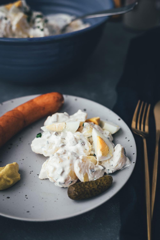 Der Klassiker: Kartoffelsalat mit Würstchen! Hier verrate ich unser Familienrezept für klassischen Kartoffelsalat mit Mayonnaise. Er wird mit Gurken, Schnittlauch und Ei zubereitet und passt perfekt zu Wiener Würstchen oder Bockwürstchen mit Senf. Auch als Grillbeilage zu Bratwürstchen ist er im Sommer perfekt. Im Winter schmeckt er zu Weihnachten, zum Beispiel klassisch an Heiligabend oder auch an Silvester. | moeyskitchen.com