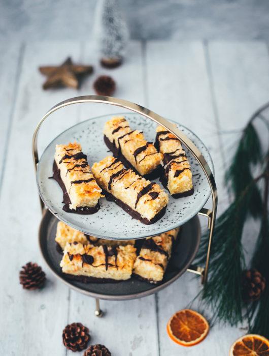 Eine tolle Abwechslung auf dem Plätzchenteller sind diese saftigen Kokos-Riegel mit Schokolade! Basis ist ein knuspriger Mürbeteig, getoppt mit einem weichen Belag aus Kokosflocken und gezuckerter Kondensmilch. Neben den ganzen Keks-Klassikern zu Weihnachten ist das eine tolle und leckere Alternative, die ich noch mit Schokolade verziere. Die Riegel erinnern von der Art her etwas an Nussecken und schmecken dezent und lecker nach Kokos. | moeyskitchen.com