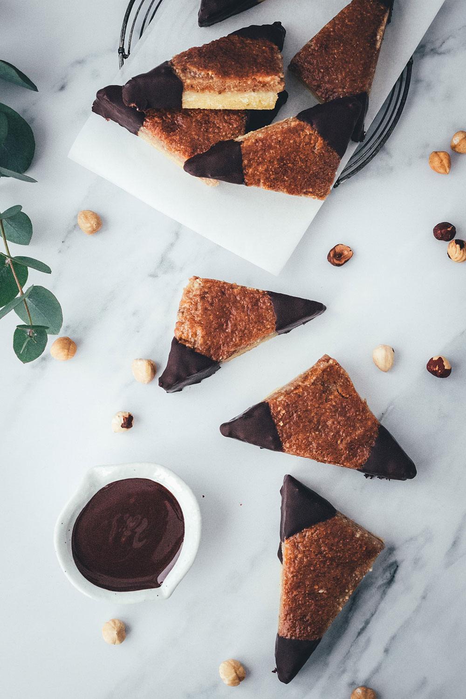 Hier habe ich das Rezept für super einfache und so saftige Nussecken. Ein einfacher Mürbeteig wird mit Aprikosenkonfitüre und einer saftigen Nussmasse mit Haselnüssen belegt und gebacken. Die Zubereitung ist kinderleicht und die Nussecken sind super schnell im Ofen. Sie schmecken das ganze Jahr über zu jeder Gelegenheit, passen aber auch hervorragend zu Weihnachten und in die Adventszeit, dank reichlich Nüssen und Schokolade | moeyskitchen.com