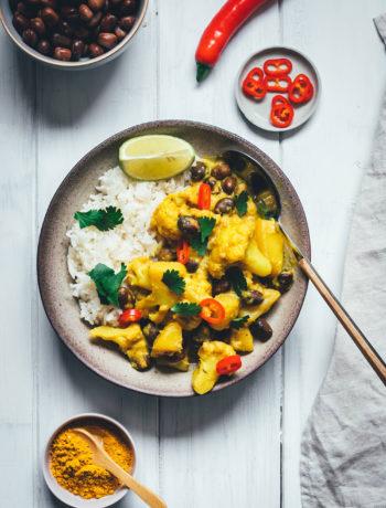 Rezept für ein würziges Blumenkohl-Kartoffel-Curry mit Ackerbohnen. Heimischer Gemüseeintopf, der an indisches Aloo Gobi bzw. Aloo Gobhi erinnert. Ackerbohnen als regionale Körnerleguminosen sind eine tolle Proteinquelle und außerdem ballaststoffreich. Und eine tolle heimische Alternative zu Kichererbsen und anderen Hülsenfrüchten. Perfekt für vegetarische und gesunde Gerichte. Madras Curry, Ingwer und Knoblauch sorgen für Würze, Chili außerdem für etwas Schärfe. Hier gibt es das einfache und unkomplizierte Rezept zum Nachkochen! | moeyskitchen.com