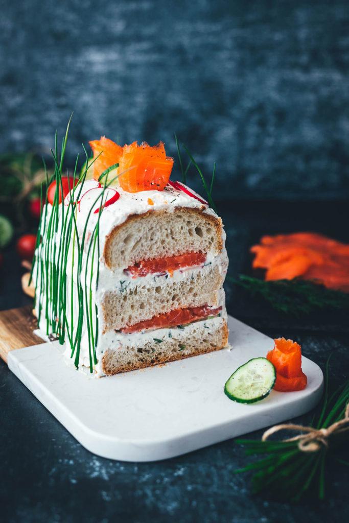 Perfekt für den Oster-Brunch oder das Sonntagsfrühstück: Herzhafte Sandwich-Torte mit geräucherter Fjordforelle, Gurke, Radieschen und Frischkäse-Creme. Aus frischem Kastenweißbrot so lecker und bunt verziert ein echter Hingucker! Diese Torte ist super einfach hergestellt und besteht aus wenigen guten Zutaten. Meine herzhafte Sandwich-Torte erinnert an die schwedische Smörgåstårta, die man traditionell zu Midsommar serviert. Sie passt aber auch einfach hervorragend in den Frühling und sieht auch als Mitbringsel großartig aus! | moeyskitchen.com