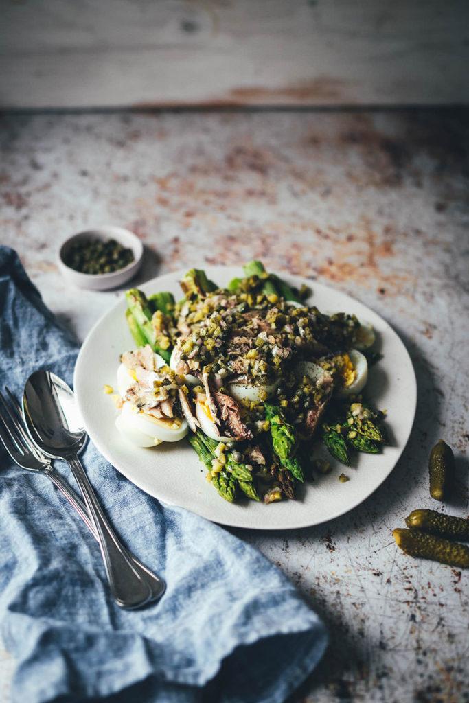 Rezept für würzigen Spargelsalat aus ofengeröstetem grünen Spargel mit einer Kapern-Vinaigrette, Sardinen und Ei. Blitzschnell auf dem Tisch und mit knusprigem Brot und einem Glas kühlen Weißwein perfekt für laue Frühlings- oder Sommerabende auf dem Balkon! Würzige Kapern, Cornichons und Schalotten geben der Vinaigrette Pfiff und harmonieren fantastisch zu den Ölsardinen aus der Dose und dem hart gekochten Ei | moeyskitchen.com