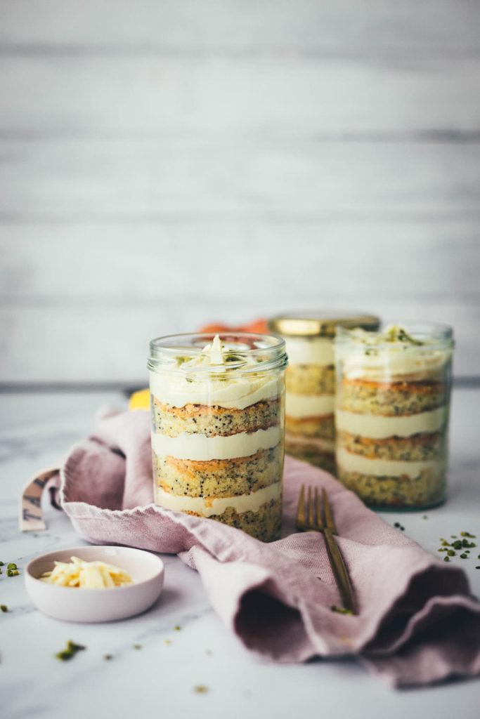 Entzückende Zitronen-Mohn-Törtchen mit weißer Schokoladen-Ganache – als kleine Torte im Einmachglas geschichtet und damit perfekt zum Mitnehmen und Verschenken! Saftiger Rührkuchen wird auf dem Blech gebacken, ausgestochen und abwechselnd mit einer leckeren Schoko-Ganache ins Glas drapiert. Gut verschlossen halten die kleinen Törtchen ein paar Tage im Kühlschrank. Auch perfekt für das Picknick draußen oder einen Spaziergang, zum Beispiel als Geburtstagstorte für eine Person oder einen anderen schönen Anlass. Es gibt immer einen Grund zu feiern! | moeyskitchen.com
