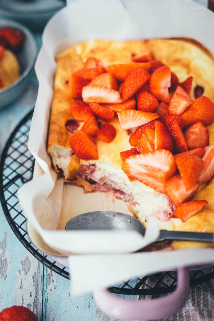 Rezept für luftigen Quark-Auflauf mit Erdbeeren. Leckeres, nicht zu süßes Dessert oder Frühstück für die ganze Familie! Magerquark wird dazu einfach mit Ei und Grieß locker aufgeschlagen und dann mit Erdbeeren in einer Auflaufform gebacken. Anschließend lauwarm mit frischen Erdbeeren serviert, so dass es an einen leckeren, aber unheimlich einfachen Käsekuchen erinnert. | moeyskitchen.com